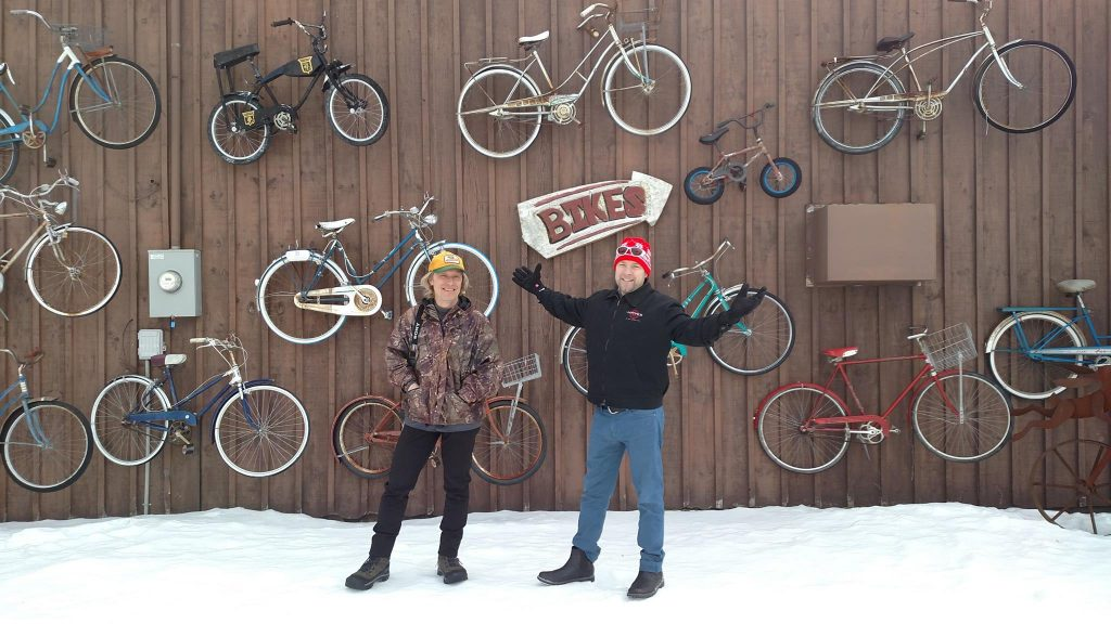 Dave Schlabowske and Matt Gissibl in front of a wall of bikes hanging on the side of the Chequamegon MTB Festival building.