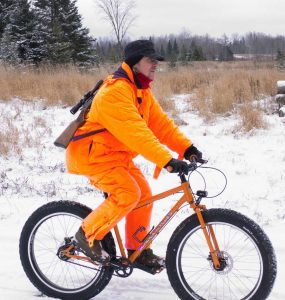 Dave Schlabowske in blaze orange on a fat bike with a rifle