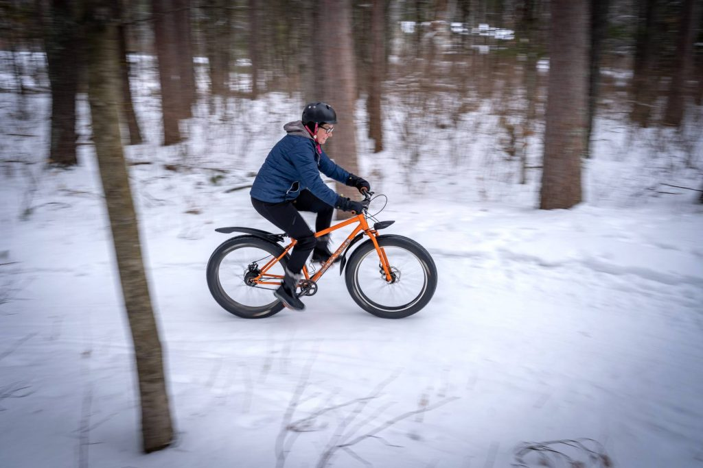 A woman smiling while riding a fat bike in winter
