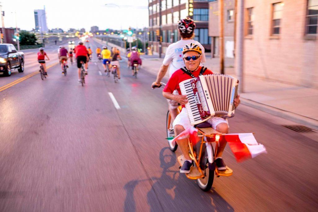 man playing accordion on back of cargo bike