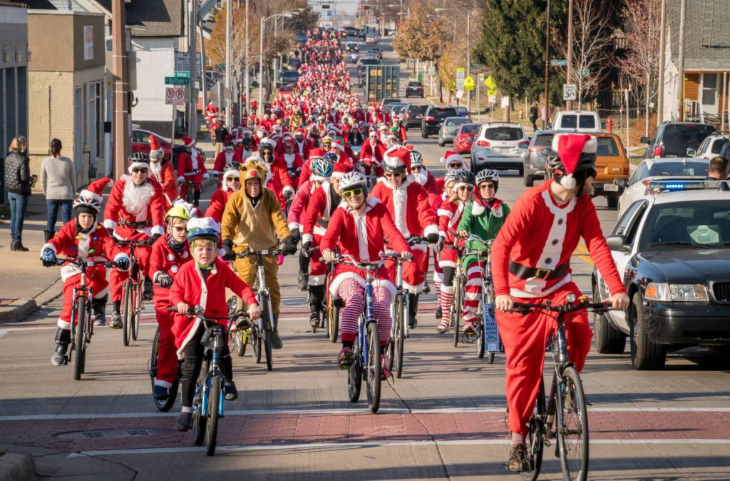 People dressed in Christmas costumes riding bicycles on a street in the Santa Cycle Rampage
