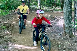 A girl rides a mountain bike in front of her father on the Hatchery Creek Trail