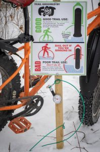 Fat bike parked outside by sign showing proper tire pressure and a tire gauge.