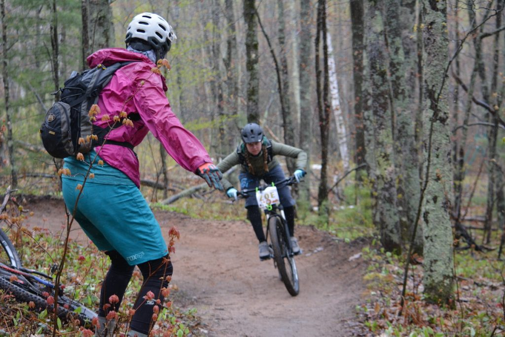A woman MTB coach watches as a woman on a mountain bike rides toward her on a trail in the woods.