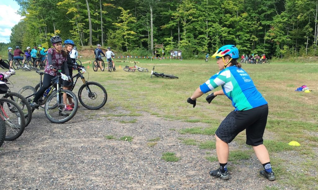 A woman wearing a bike helmet coaches other women on bikes in a grassy field.