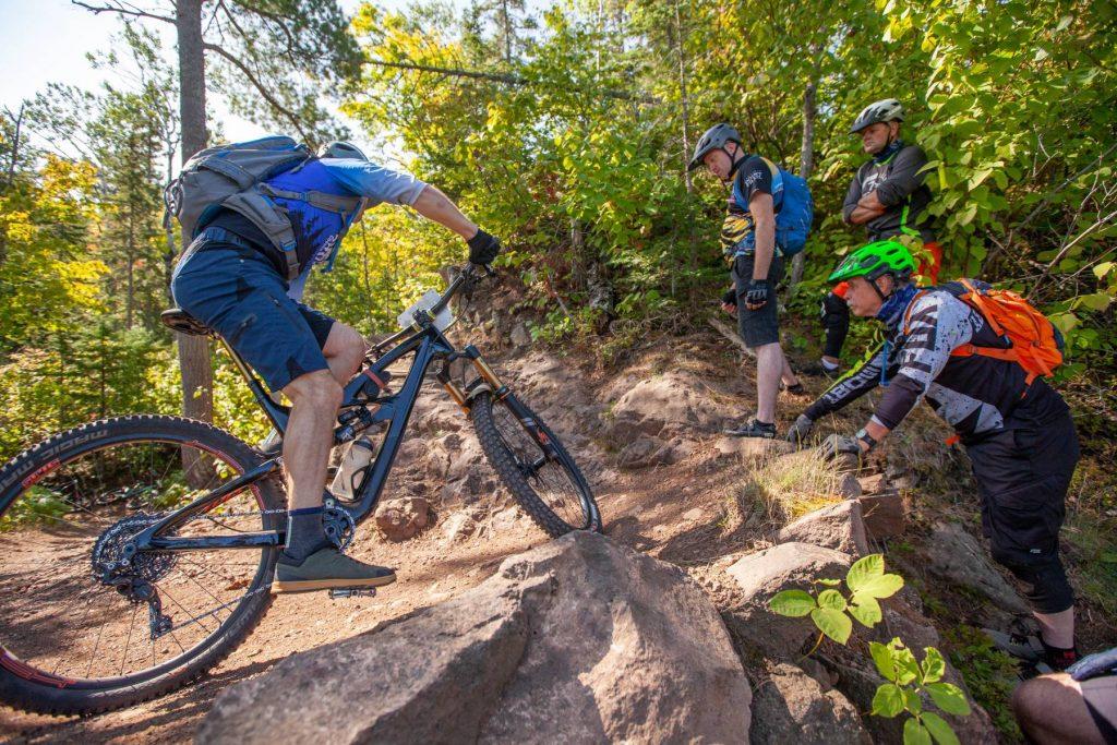 Men in bike helmets watch as a man on a mountain bike rides a bermed bank on a trail