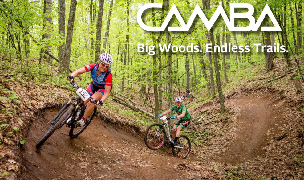 A woman rides a mountain bike on a banked turn through the forest with a man following her on a mtb.