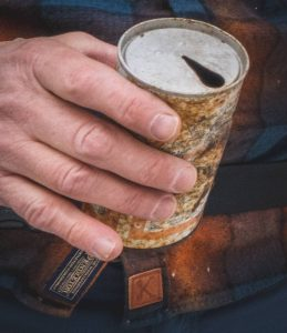 hand holding old beer can