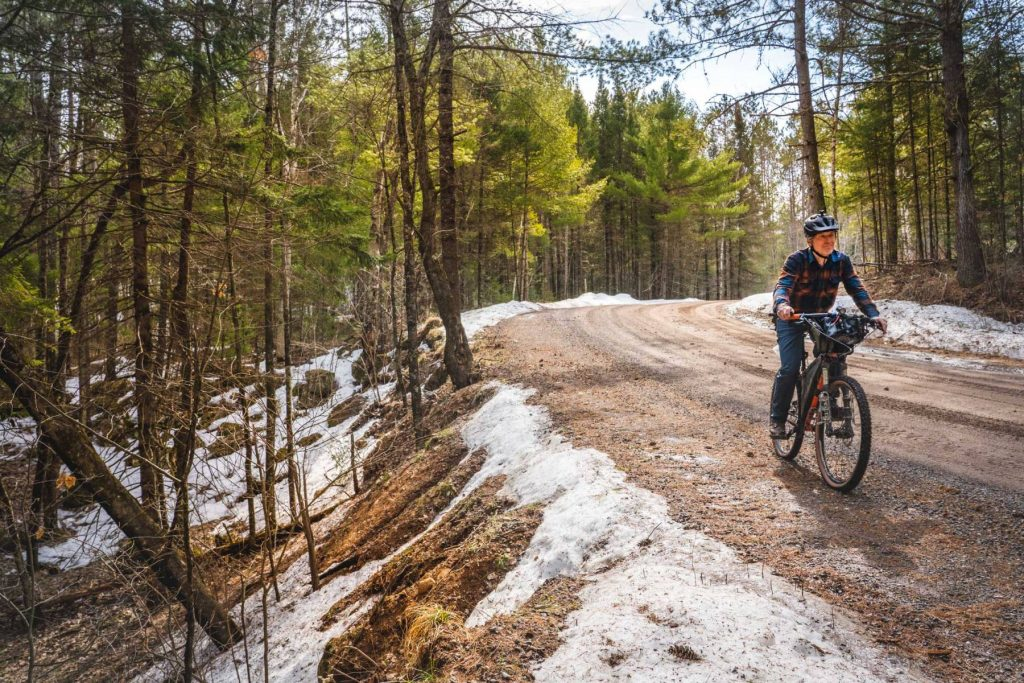 man riding a bike on a gravel road though the forest in early spring