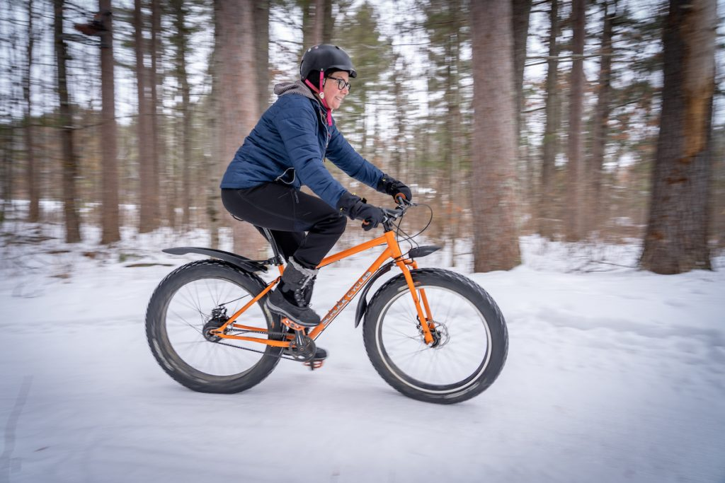 woman rides a fat bike in winter with trees in background