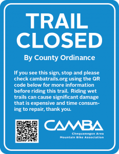 Blue Trail Closed Sign that says Trail Closed By County Ordinance If you see this sign, stop and please check cambatrails.org using the QR code below for more information before riding this trail. Riding wet trails can cause significant damage that is expensive and time consuming to repair, thank you.